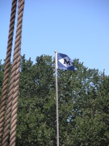A view of the Mystic Seaport flag on shore, from the Amistad.