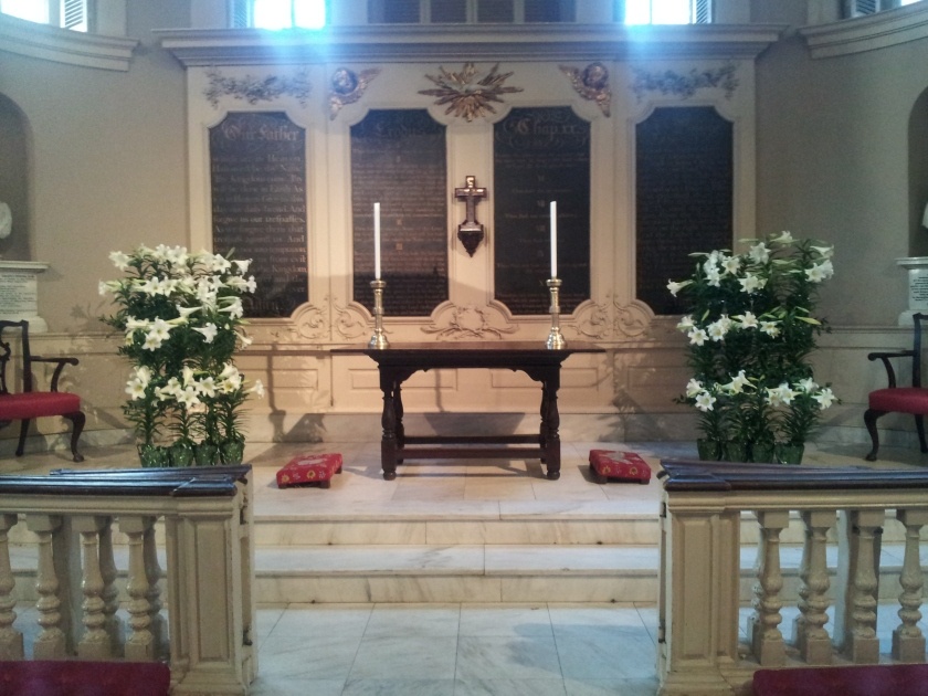 These two racks on either side of the communion table are full of lilies.