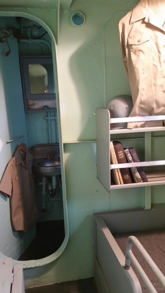 View of the captain's sea cabin showing door to his private head.  Note the helmet on the shelf.